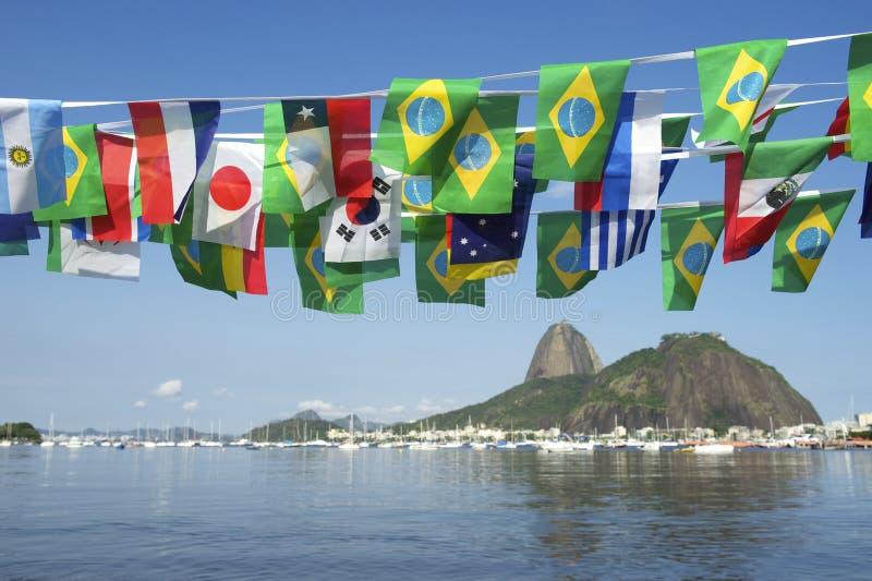 El International brasileño señala la montaña Rio de Janeiro Brazil de Sugarloaf por medio de una bandera fotos de archivo libres de regalías