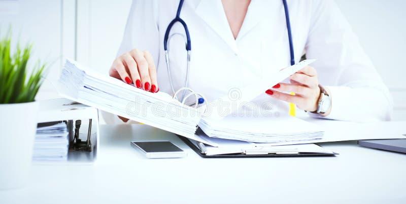 El interno médico o el doctor de sexo femenino da la búsqueda para los expedientes pacientes del ` s en oficina Trabajo administr foto de archivo