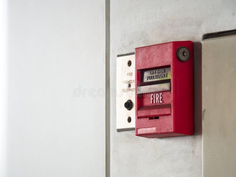 El interruptor de botón, la alarma de incendio en la pared gris para la alarma y el sistema de seguridad con el extintor viran ha fotos de archivo
