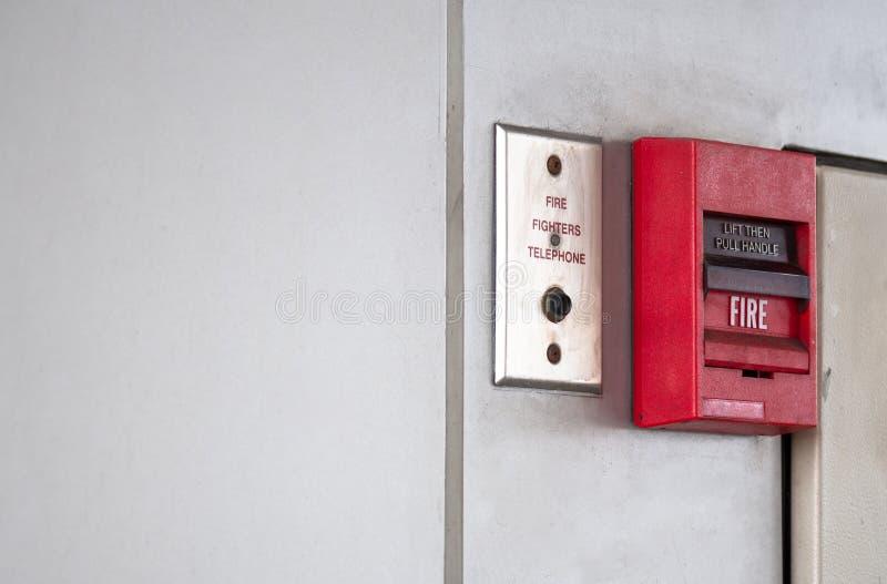 El interruptor de botón, la alarma de incendio en la pared gris para la alarma y el sistema de seguridad con el extintor viran ha foto de archivo libre de regalías