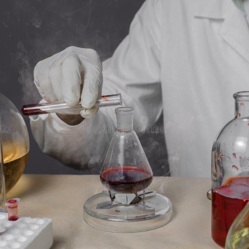 El investigador médico o científico de sexo masculino del laboratorio realiza pruebas con el líquido rojo Cierre para arriba imagenes de archivo