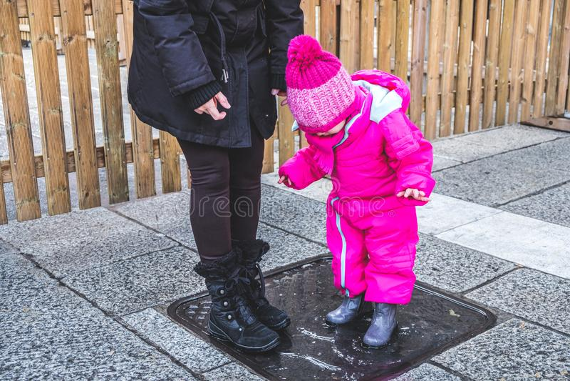 El invierno del charco del bebé patea a la hembra con la mamá fotografía de archivo