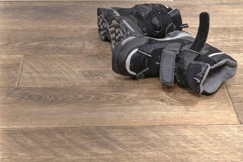 El invierno embroma las botas negras abandonadas fotografía de archivo
