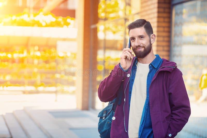 El invierno que lleva del hombre joven viste con un smartphone en su mano, caminando en la calle Llamarada de Sun imagenes de archivo