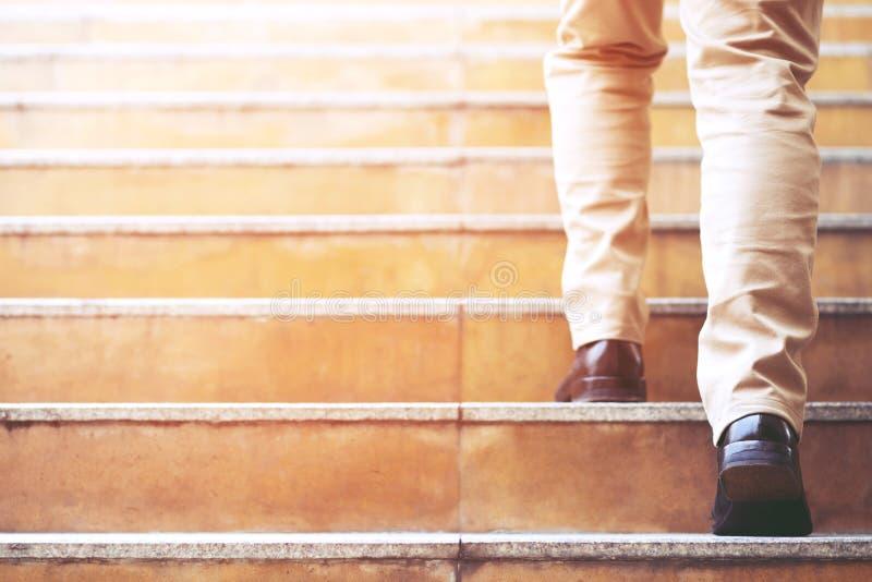 El ir del escalonamiento de negocios que camina de la persona joven del hombre uno para arriba las escaleras fotos de archivo