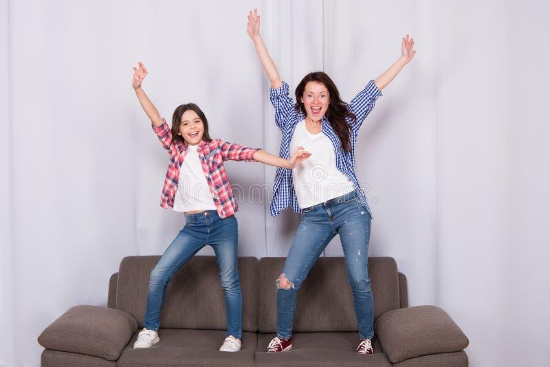 El ir loco junto El día de los niños Madre y niño en el país Día de la familia La niña ama a su madre salta en el sofá imagen de archivo