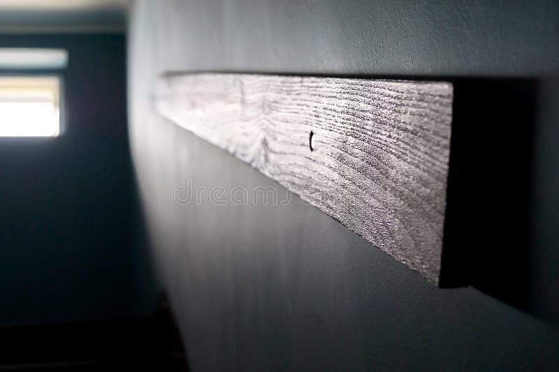 El ir para arriba las escaleras: Barandilla de madera montada en la pared oscura para las escaleras, ventana brillante en la unid foto de archivo libre de regalías