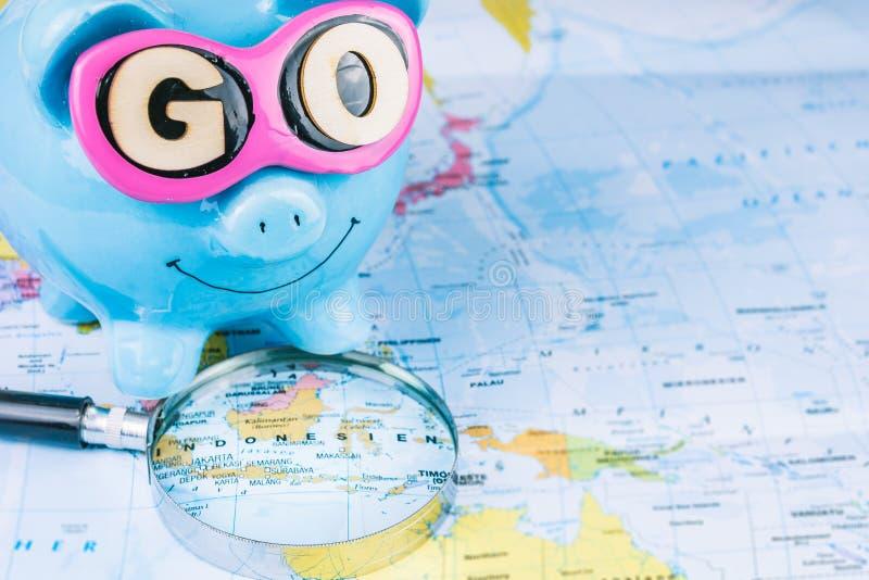El ir a viajar Lupa que pone en el mapa La hucha del ahorro con las gafas de sol y VA lema que permanece en el mapa del mundo imagen de archivo