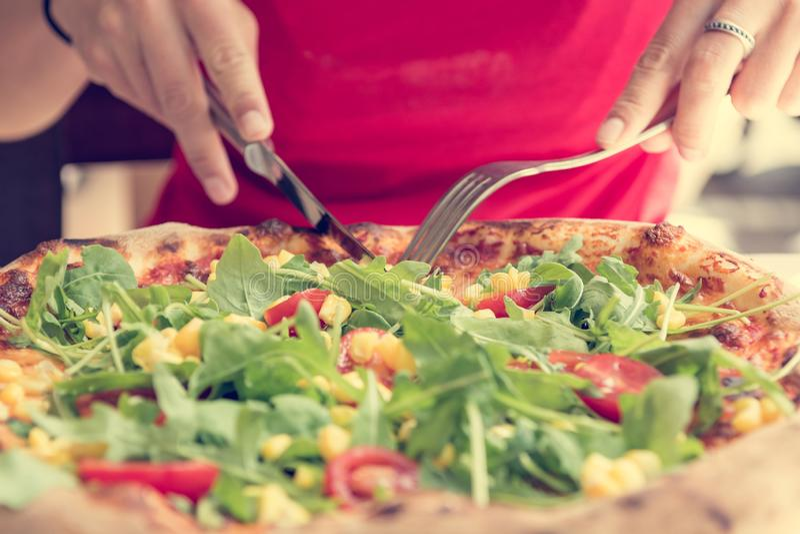 El italiano delicioso diseñó la pizza vegetal con los tomates, el maíz y el rucola imagenes de archivo