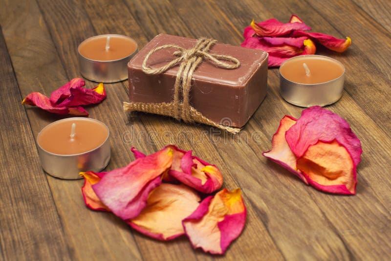 El jabón de baño con la vela y seca el pétalo color de rosa imagen de archivo