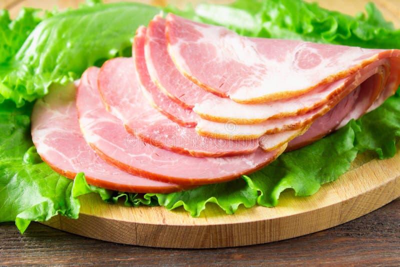 El jamón cortado con lechuga verde fresca se va en una tabla de cortar redonda Productos de carne en una tabla de madera marrón imagenes de archivo