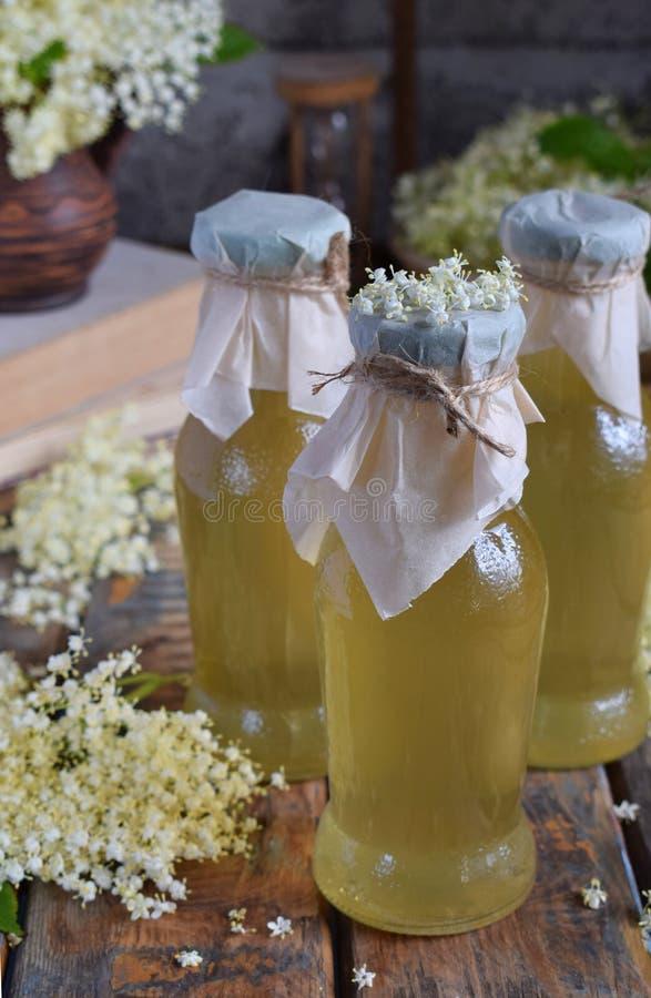 El jarabe y el flor cordiales de Elderflower florecen en fondo de madera Las flores comestibles de la baya del saúco añaden sabor fotografía de archivo libre de regalías