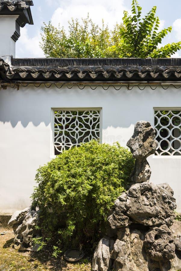 El jardín de rocalla y la planta ajardinan delante de la pared blanca imagen de archivo