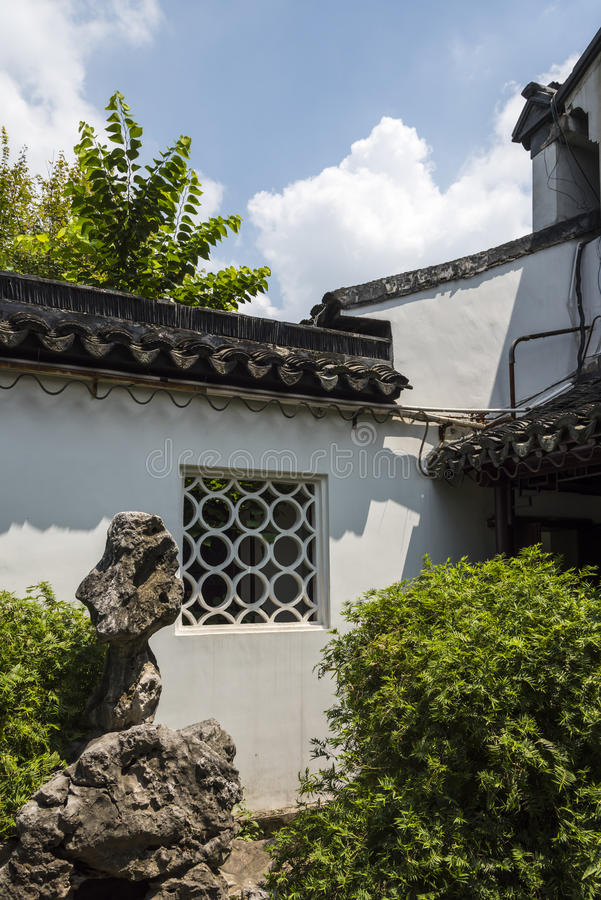 El jardín de rocalla y la planta ajardinan delante de la pared blanca imagen de archivo libre de regalías