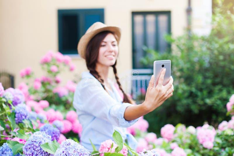 El jardinero de la mujer toma el selfie La muchacha es sonriente y con el teléfono móvil en el jardín del campo de la hortensia fotos de archivo libres de regalías