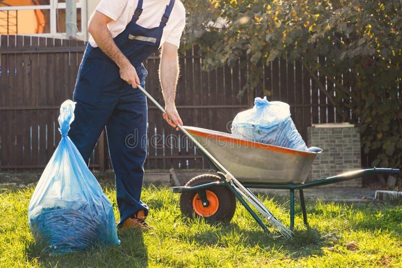 El jardinero limpia las hojas en la yarda Al lado de él es un carro con estiércol vegetal fotografía de archivo libre de regalías