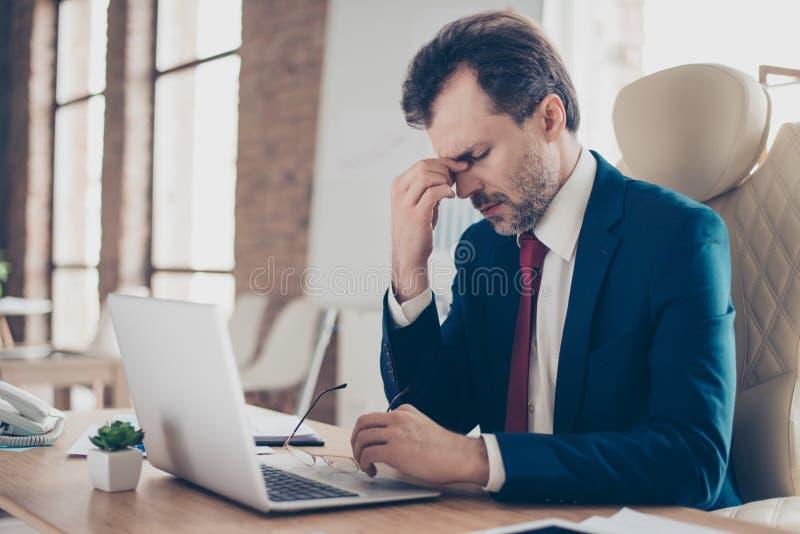 El jefe agotado está sosteniendo su puente de la nariz con los ojos cerrados, él i imagenes de archivo