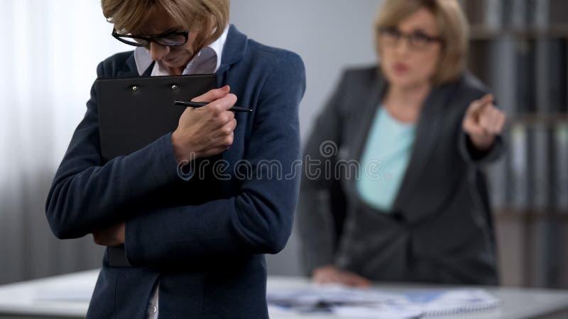 El jefe de la señora golpea hacia fuera al empleado con el pie de sexo femenino triste de la oficina, terminación del empleo imagen de archivo libre de regalías
