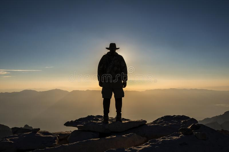 """El Jefe de la Sierra Nevada, Summit of Mt Whitney. """"El Jefe de la Sierra Nevada"""" is a self portrait of a hiker eclipsing the sun at sunrise on the stock photography"""
