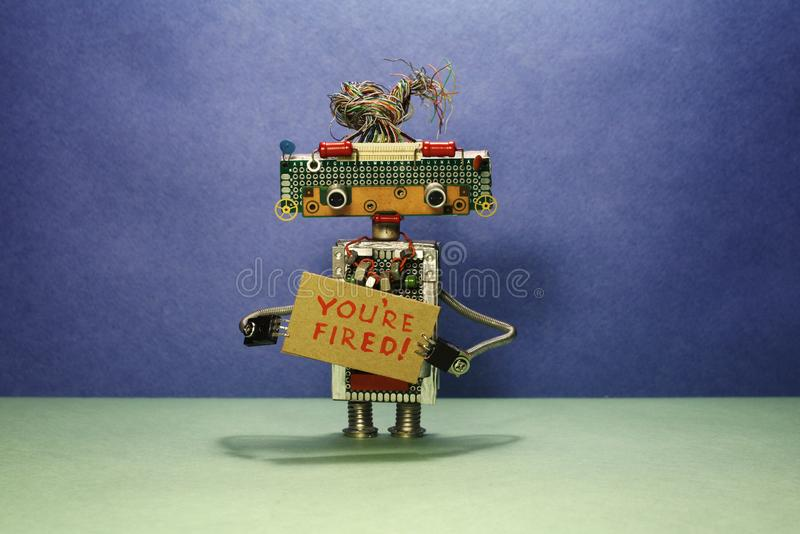 El jefe del robot despide personales El robot muestra la muestra de la cartulina con el texto que le encienden Fondo del verde az foto de archivo libre de regalías