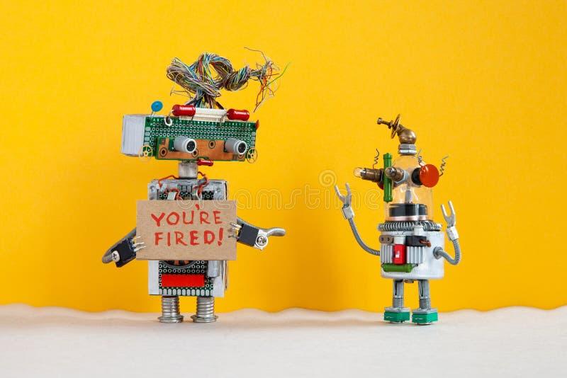 El jefe del robot despide a un patrón robótico más joven Carácter robótico con una muestra de la cartulina y texto manuscrito ust imagenes de archivo