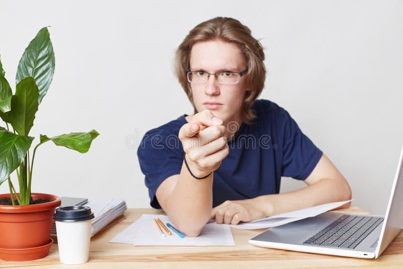 El jefe masculino estricto serio se sienta en el interior de la oficina, puntos con el índice en usted, advierte sobre el castigo foto de archivo