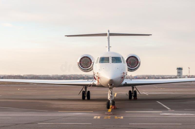El jet de lujo del negocio se coloca en el aeropuerto y alista para subir Vista delantera de los aviones privados imagen de archivo