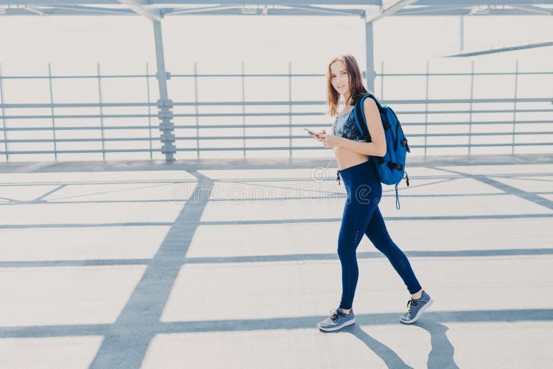 El joven bastante femenino tiene paseo afuera, lleva la mochila, teléfono celular moderno de los controles, escucha música, compr imágenes de archivo libres de regalías