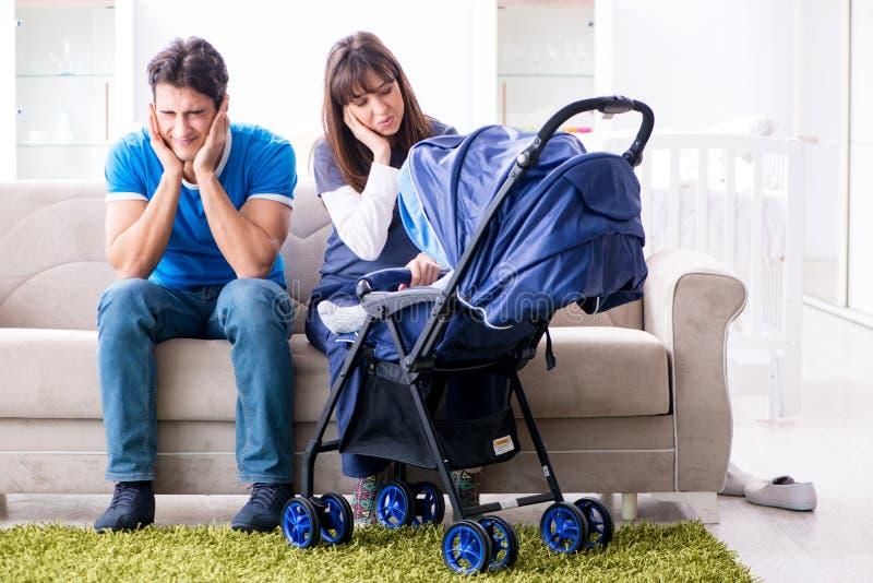 El joven parents con su bebé recién nacido en el cochecito de niño del bebé que se sienta en el sofá imagenes de archivo