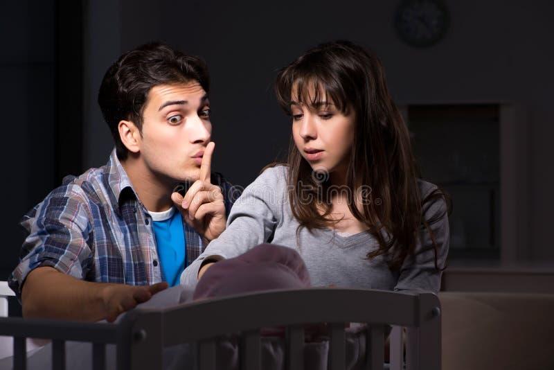 El joven parents insomne con el bebé recién nacido en la noche fotografía de archivo libre de regalías