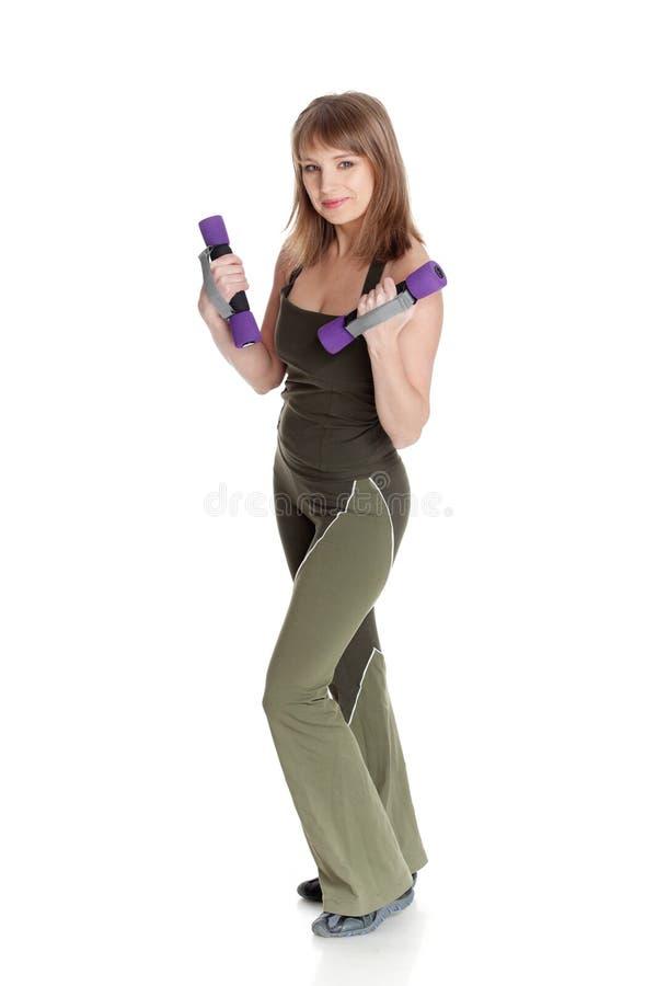 El joven se divierte a la mujer con pesas de gimnasia. imagen de archivo