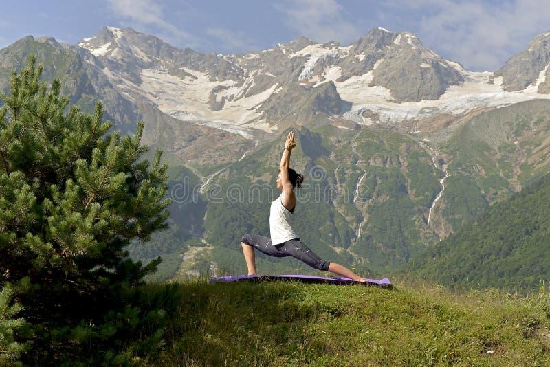 El joven se divierte a la mujer que hace yoga en el verano en el fondo de montañas nevosas fotografía de archivo libre de regalías