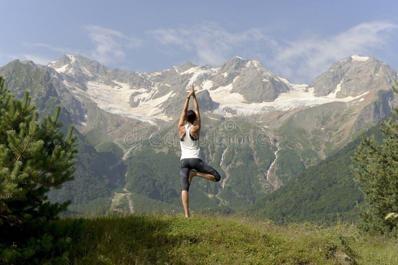 El joven se divierte a la mujer que hace yoga en el verano en el fondo de montañas nevosas fotografía de archivo
