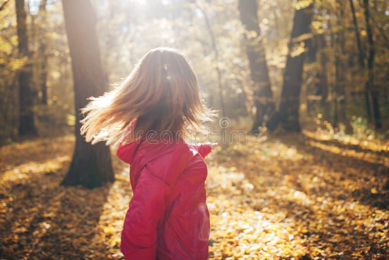 El joven se divierte los trenes de la muchacha en la madera del otoño de la mañana, parque fotos de archivo libres de regalías