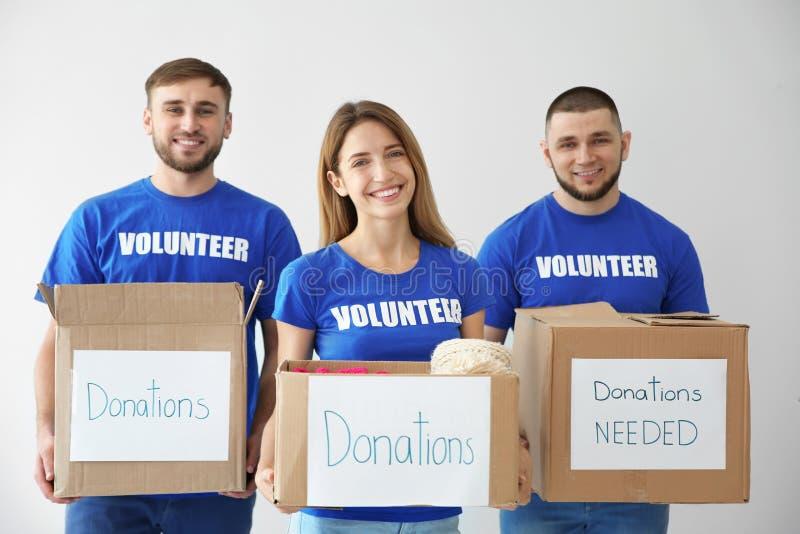 El joven se ofrece voluntariamente sosteniendo las cajas con las donaciones para la gente pobre imagen de archivo