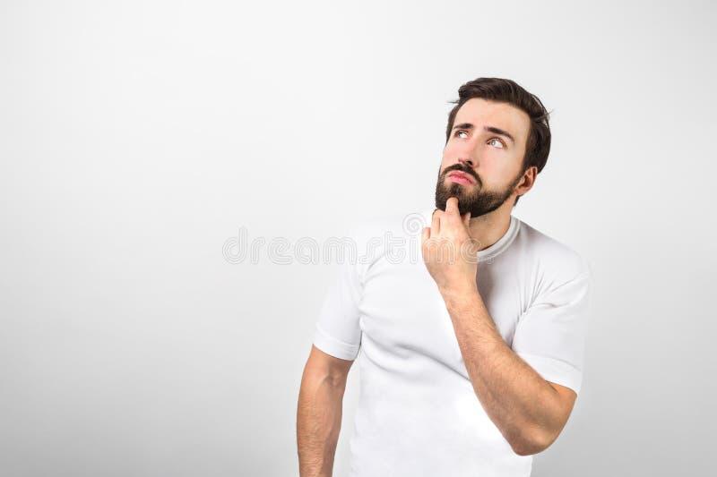 El joven y el hombre dsome de Hans se está colocando en la pared blanca y está guardando su mano izquierda cerca de la barbilla É imágenes de archivo libres de regalías