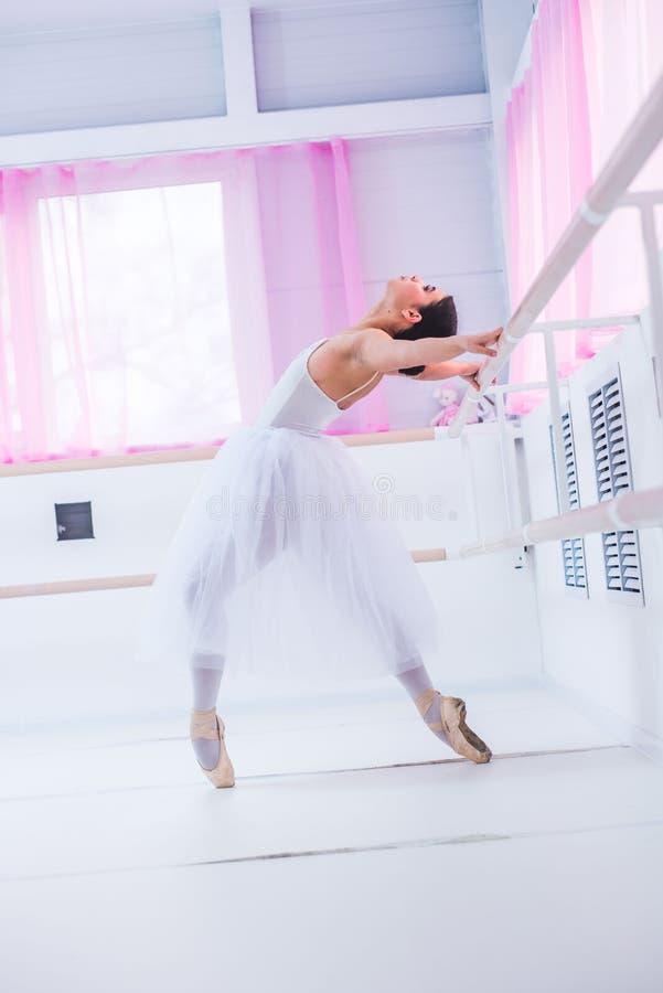 El joven y la bailarina increíblemente hermosa es de presentación y de baile en un estudio blanco por completo de la luz imagenes de archivo