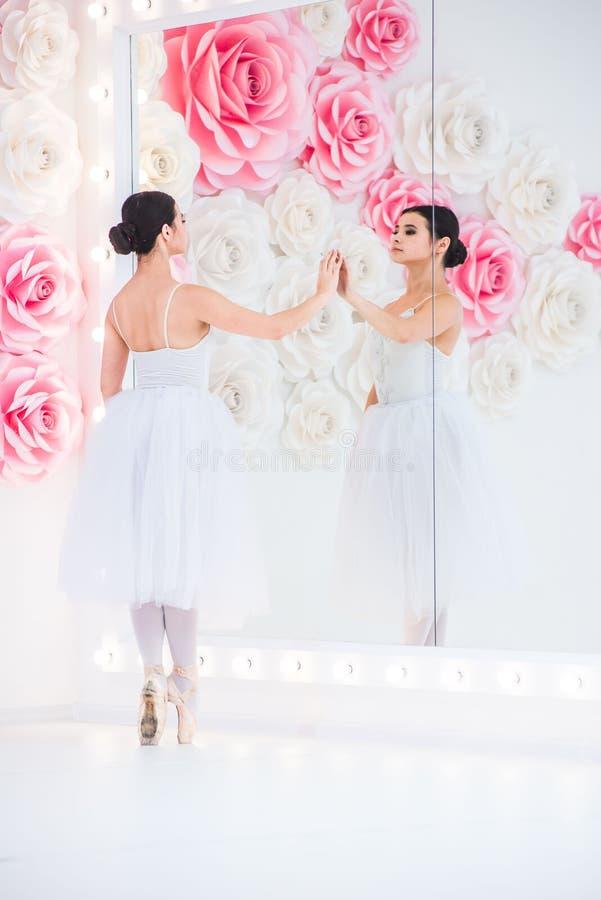 El joven y la bailarina increíblemente hermosa es de presentación y de baile en un estudio blanco por completo de la luz imagen de archivo libre de regalías