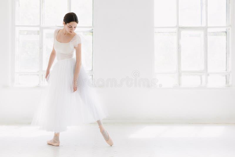 El joven y la bailarina increíblemente hermosa es de presentación y de baile en un estudio blanco imagenes de archivo