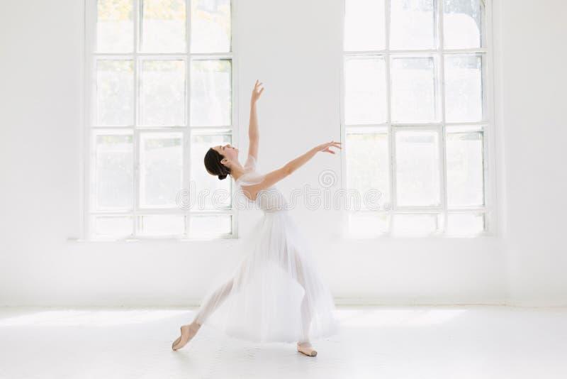 El joven y la bailarina increíblemente hermosa es de presentación y de baile en un estudio blanco fotos de archivo