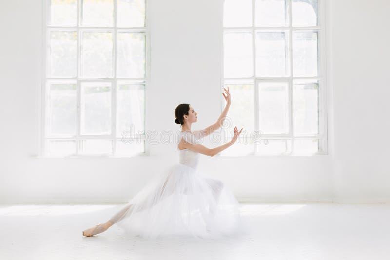 El joven y la bailarina increíblemente hermosa es de presentación y de baile en un estudio blanco foto de archivo