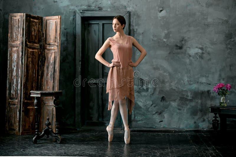El joven y la bailarina increíblemente hermosa es de presentación y de baile en un estudio negro fotos de archivo