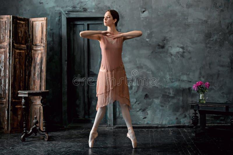 El joven y la bailarina increíblemente hermosa es de presentación y de baile en un estudio negro fotografía de archivo