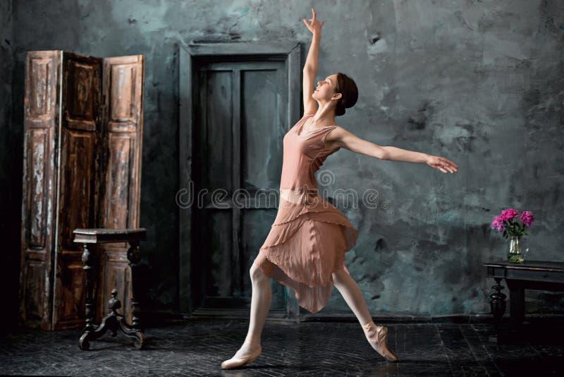 El joven y la bailarina increíblemente hermosa es de presentación y de baile en un estudio negro fotografía de archivo libre de regalías