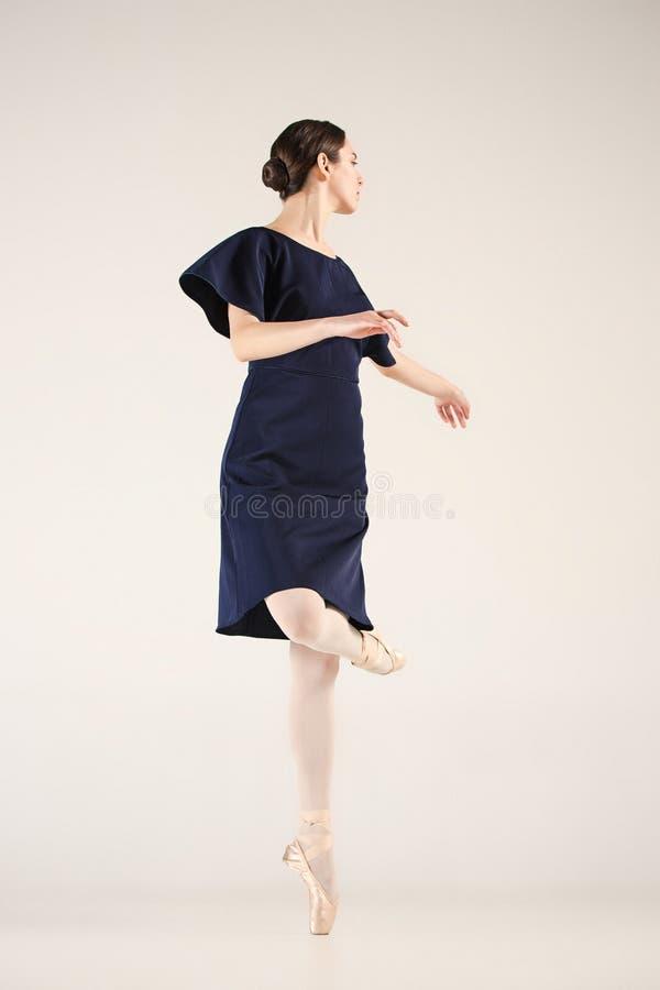 El joven y la bailarina increíblemente hermosa está bailando en un estudio azul foto de archivo