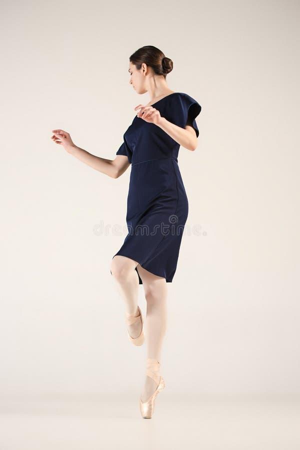 El joven y la bailarina increíblemente hermosa está bailando en un estudio azul foto de archivo libre de regalías