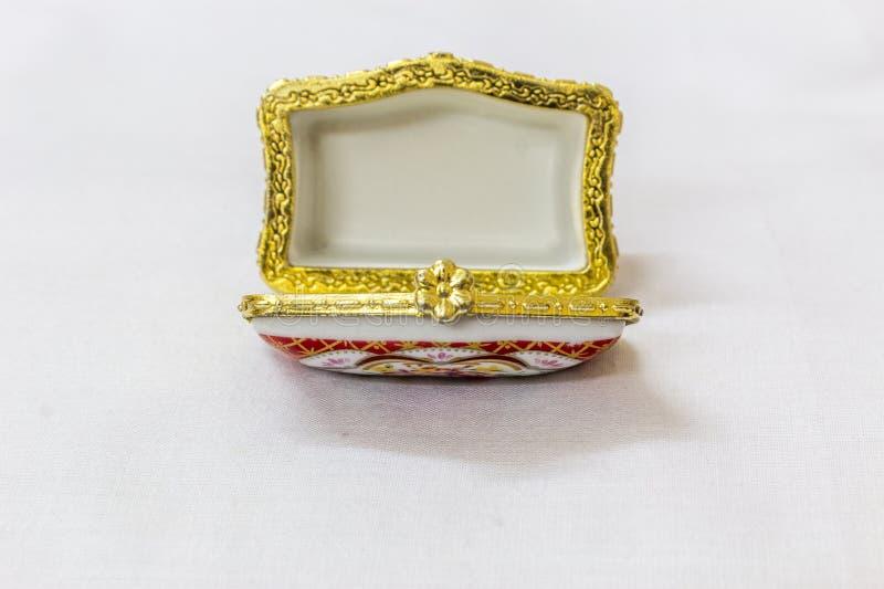 El joyero colorido minúsculo con oro platted la encrespadura en un fondo blanco Macro con la profundidad del campo extremadamente foto de archivo libre de regalías