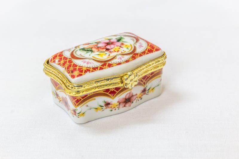 El joyero colorido minúsculo con oro platted la encrespadura en un fondo blanco Macro con la profundidad del campo extremadamente foto de archivo