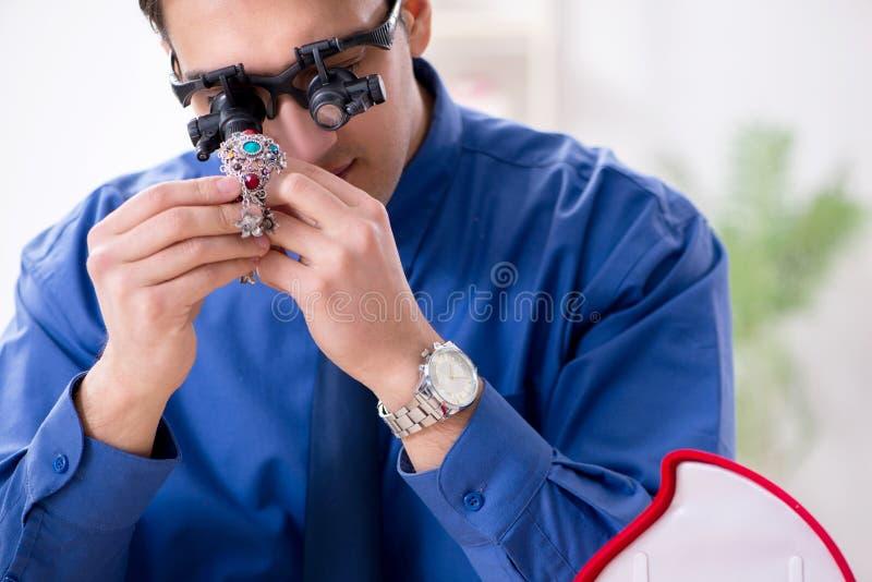 El joyero que trabaja con joyería de lujo en el taller foto de archivo libre de regalías