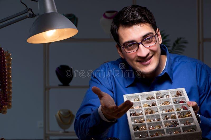 El joyero que trabaja en su taller tarde en la noche imagen de archivo